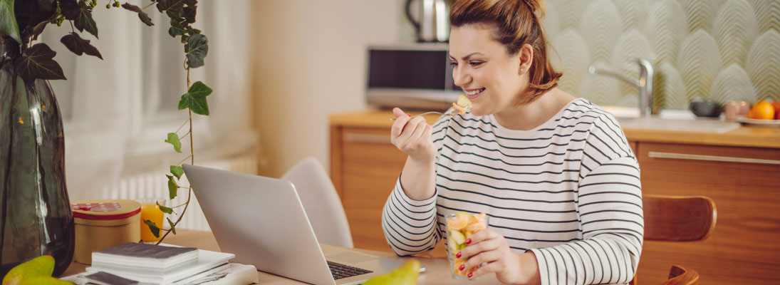 woman eating fruit and using laptop computer