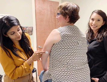 UCSF Fresno's Varsha Babu, MD, helps Annette Simmons test her glucose levels with a shot in the back of the arm.
